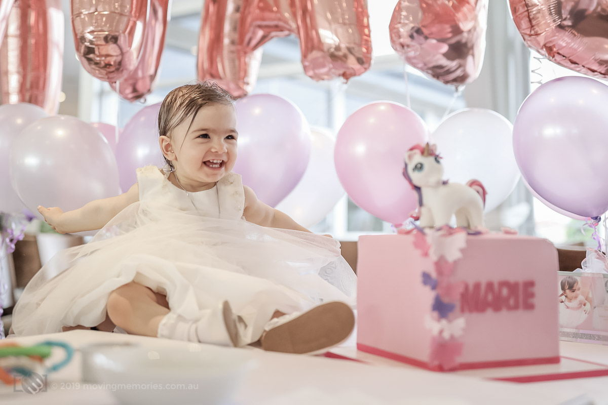 baby Marie with her unicorn pink cake and decorations during her Greek Orthodox Christening reception at Bayblu Seafood Restaurant Blakehurst south of Sydney