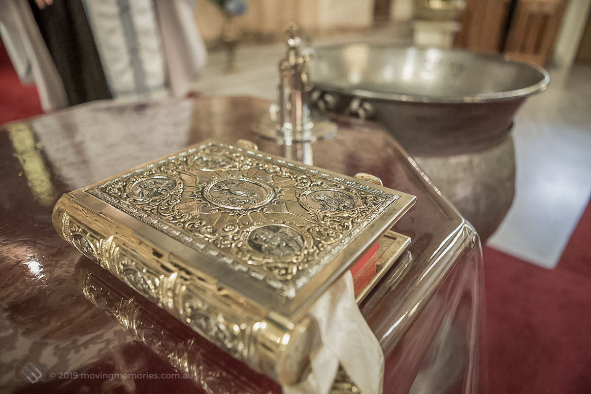the Holy Bible on the altar with the Baptism font and ornate vessel in the background at St. Gerasimos Greek Orthodox Church in Leichhardt Sydney