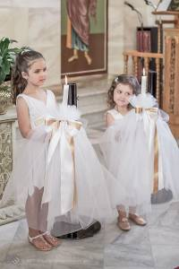 young sisters at the altar hold the candles, known as Lambada, used in a Greek Orthodox Christening in Sydney