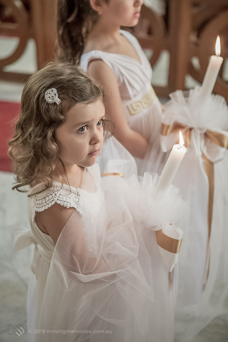 young girls at the altar hold the candles, known as Lambada, used in a Greek Orthodox Christening in Sydney