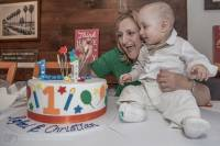 a baby twin boy with his mother takes joy in the sight of his colourful birthday cake also celebrated at the baby's Greek Orthodox Christening reception at Tavernaki Greek Restaurant Sydney