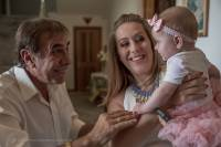 a baby girl held by her mother as the proud grand father gets a smile from the baby girl at a Greek Orthodox Church in Sydney