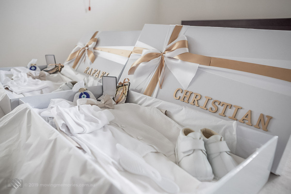 boxes decorated with ribbon and the child's name holding some things needed for a Greek Orthodox Christening including the baby's shoes, white singlet clothes and bath towel, a Crucifix