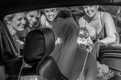 Sydney Bride Rachel arriving at her wedding ceremony. Greeted by her bride's maids as the bride is about to step out of the bridal Ford Mustang at the Lakes Sydney