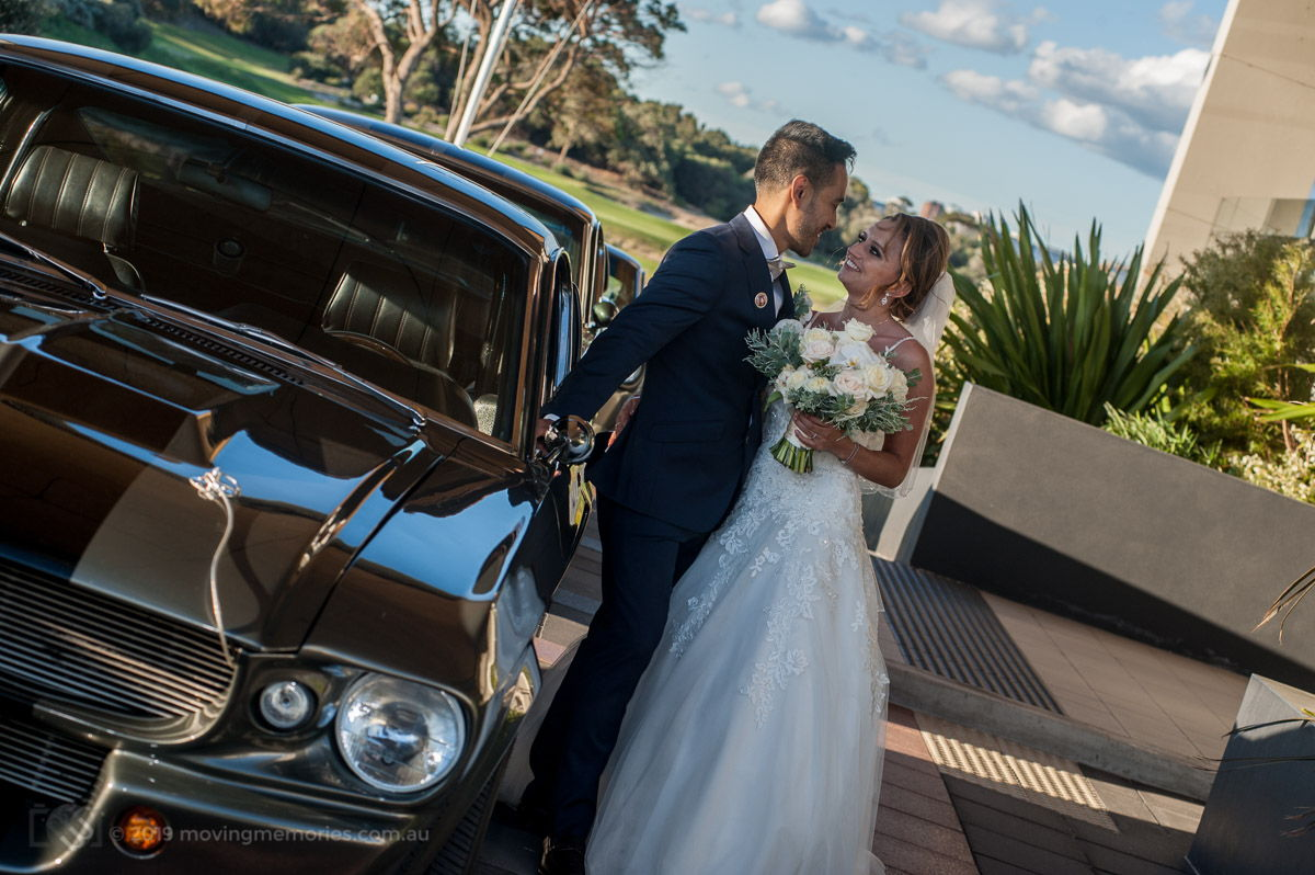 Sydney Groom Ermel, with his Bride Rachel, embrace with their Ford Mustang wedding cars in the background at the Lakes Sydney