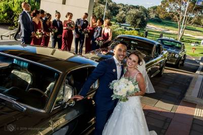 Sydney Groom Ermel, with his Bride Rachel, posing for a shot with their Ford Mustang wedding cars and their bridal party in the background at the Lakes Sydney