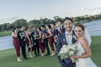 Sydney Groom Ermel, with his Bride Rachel, posing for a shot with their bridal party in the background by the lake at the Lakes Sydney