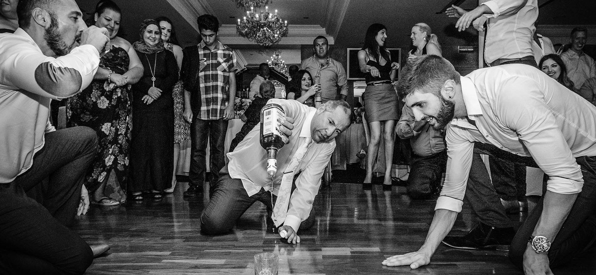 Sydney-Wedding-Video-&-Photography-at-a-Greek-wedding-pouring-bourbon-on-the-dance-floor-with-the-groom-and-his-guests