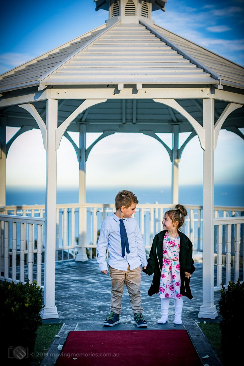 the-big-brothe-and-sister-hold-hands-in-the-garden-gazebo-before-the-guests-arrive-at-the-reception-for-Baby-Girl-Andrea-Christening-at-Panorama-House-Bulli-Tops-near-Wollongong